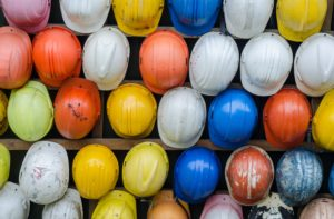 A wall of colourful construction site safety helmets