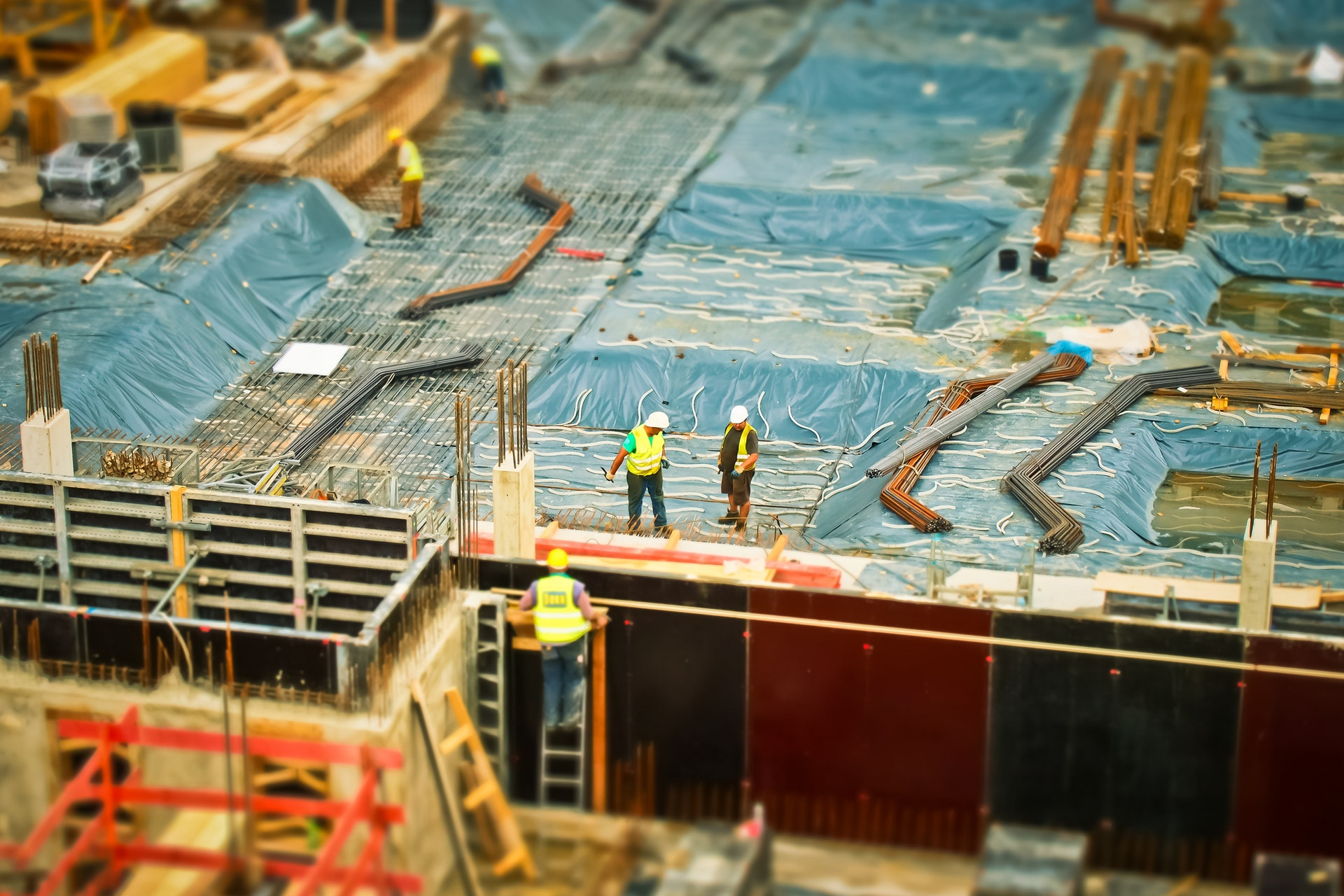 an image of construction site with three workers