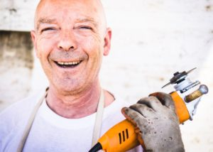 A construction worker smiling and holding a power tool
