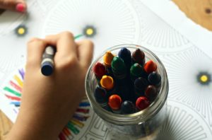 a picture of crayons with a child's hand colouring in