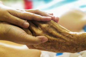 social care worker holder elderly person's hand