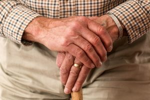 A picture of an elderly man holding a stick
