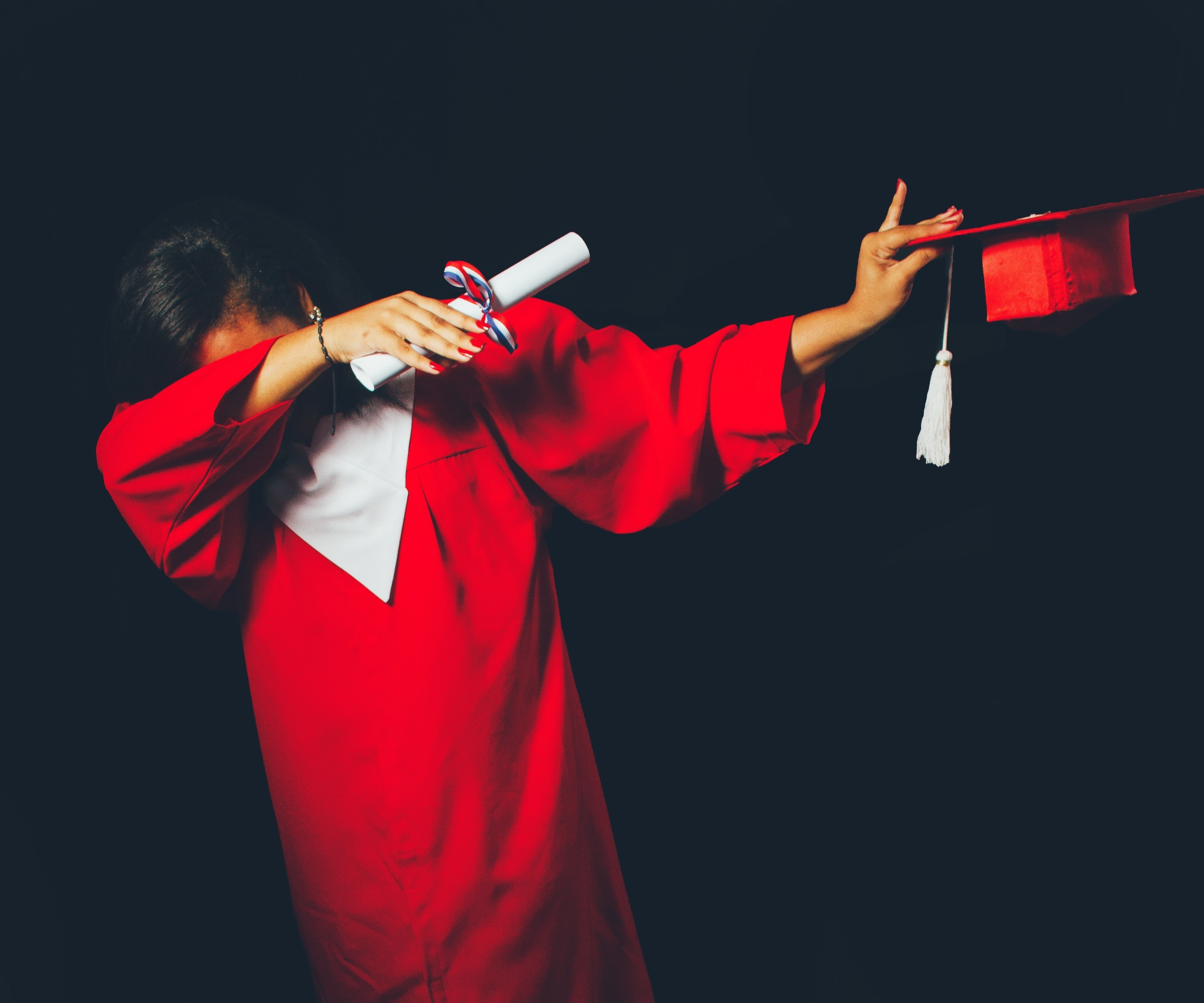 an image of university graduate posing in her graduation robe