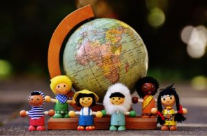 children of different nationalities standing in front of a world globe