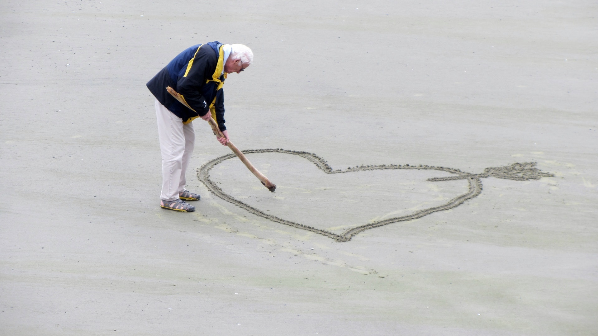 an elderly person drawing a heart in sand