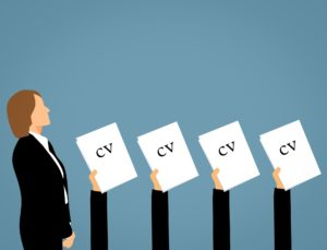 An image of a line of candidates raising their CV's above their heads