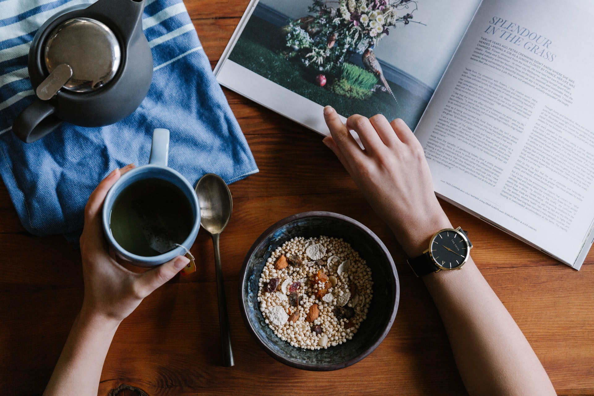 a person reading a book with a bowl of whole grain and green tea