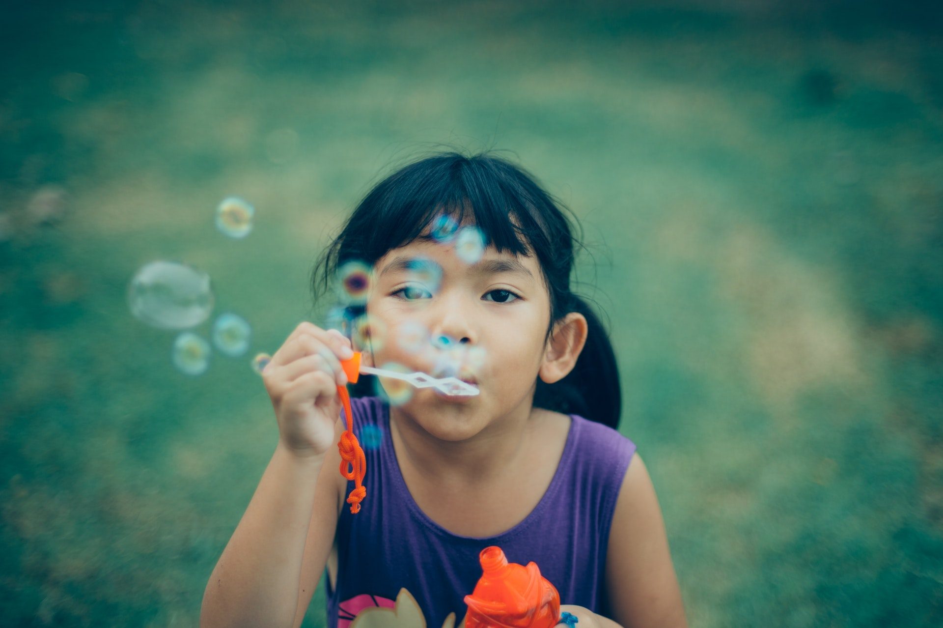 an image of a girl blowing bubbles.